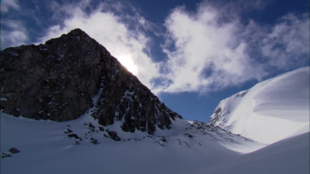 wispy clouds float above rugged mountains covered in deep snow. - british columbia stock videos & royalty-free footage