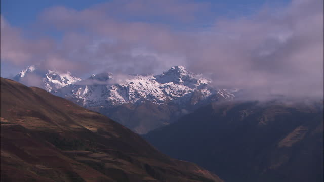 wispy clouds float through a mountain range. - wispy stock videos and b-roll footage