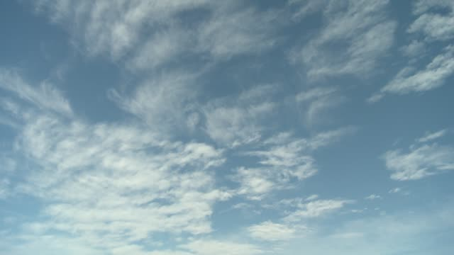 wispy clouds flow across a blue sky. available in hd. - rauchartig stock-videos und b-roll-filmmaterial