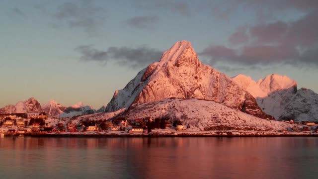 wispy clouds flow over a snow-dusted mountain at sunset. - peter snow stock videos & royalty-free footage