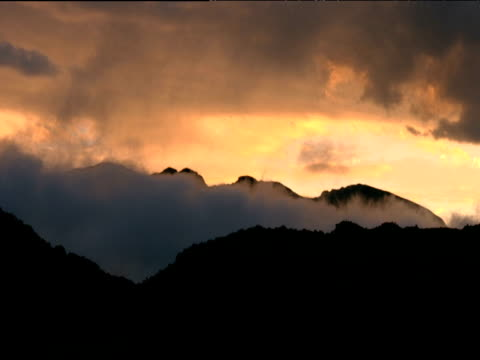 wispy clouds move past silhouetted mountain ranges at sunset south africa - wispy stock videos and b-roll footage