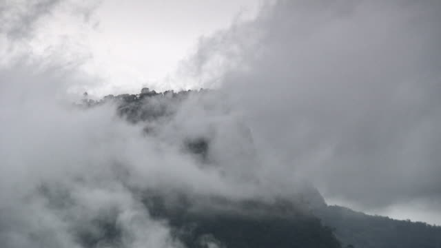 Wispy clouds obscuring forested clifftop, rural Cundinamarca region, Colombia