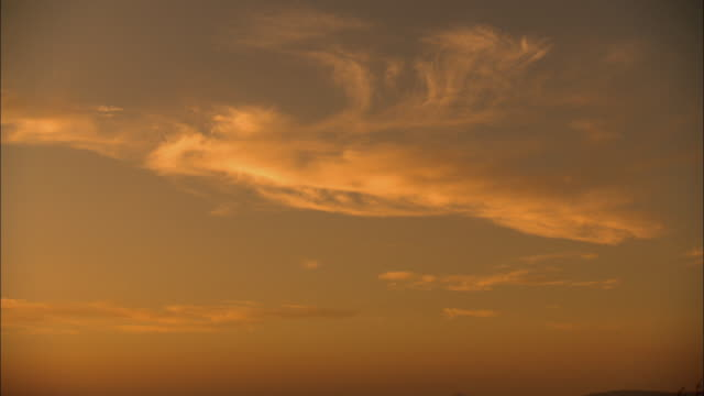 WS Wispy clouds on orange sky at sunset above Mojave Desert / California, USA