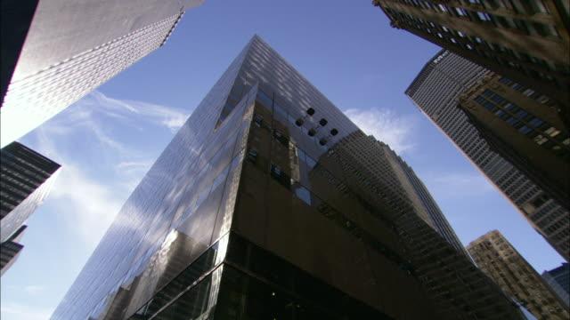wispy clouds reflect in the windows of a manhattan skyscraper. - manhattan video stock e b–roll
