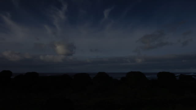 wispy clouds scud over a tree-covered coastline. available in hd. - wispy stock videos & royalty-free footage