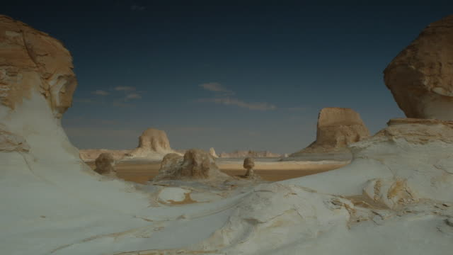 Wispy clouds skim over the rock formations in White Desert Egypt. Available in HD.