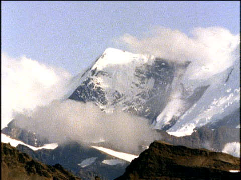 wispy clouds swirl over snow capped mountain - wispy stock videos and b-roll footage