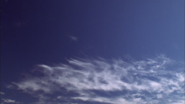 wispy white clouds in dark blue sky drift away from camera available in hd. - wispy stock videos and b-roll footage