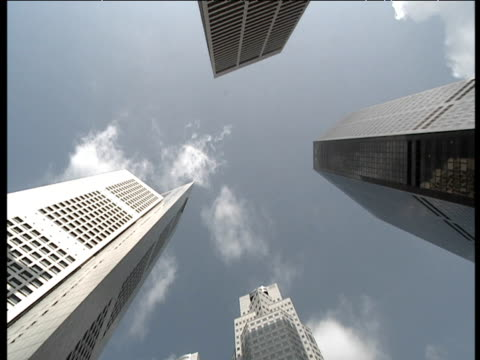 wispy white clouds pass behind skyscrapers in singapore's financial district - wispy stock videos & royalty-free footage
