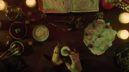 Witch blowing out candle top view. Table with spellbook for making rite. Herbs, burning candles, crystal magic ball for sacrifice. Halloween theme, full moon, witchcraft