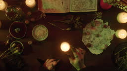Witch lighting candle top view. Table with spellbook for making rite. Herbs, burning candles, crystal magic ball for sacrifice. Halloween theme, full moon, witchcraft