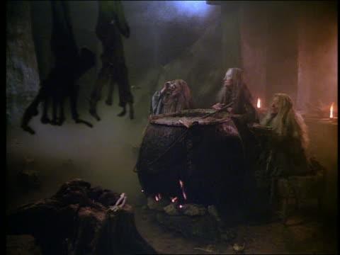 3 witches standing around cauldron