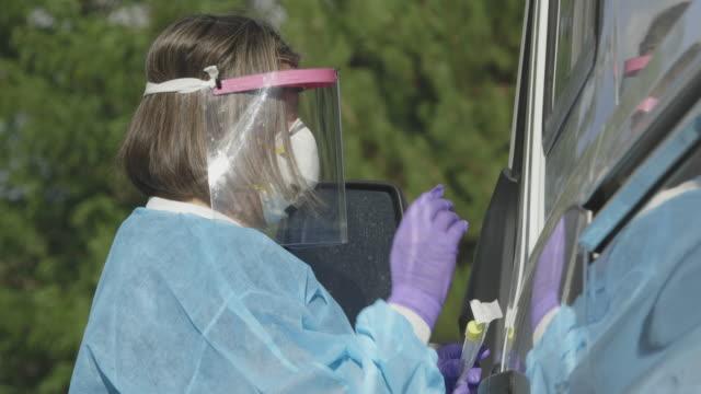 """vídeos y material grabado en eventos de stock de con un letrero """"covid-19 drive-up testing"""" en primer plano, una enfermera mujer que lleva una bata, una máscara facial quirúrgica, guantes y un escudo facial habla a un paciente de su coche en una línea de prueba covid-19 (coronavirus) fuera de una clin - trabajador de primera línea"""