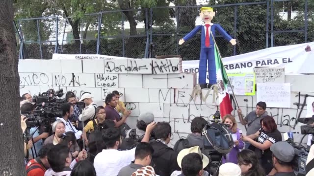 with a fake wall and burning pinatas mexicans protested on friday against new us president donald trump in front of us embassy - papier stock videos & royalty-free footage