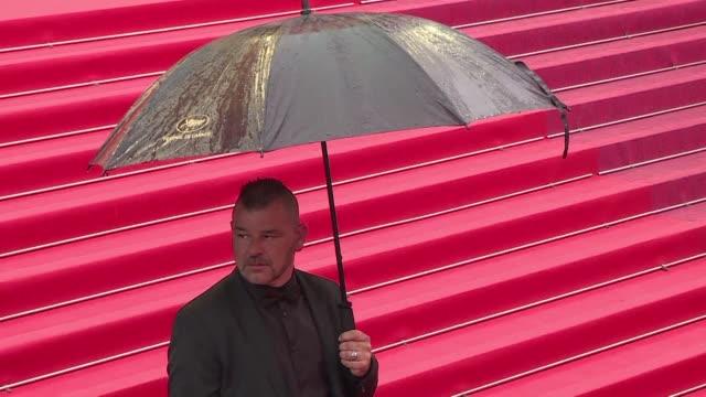 vídeos y material grabado en eventos de stock de with a parade of umbrellas on the red carpet, the cannes film festival bursts into song amid heavy downpour to the sound of singin in the rain ahead... - sumar