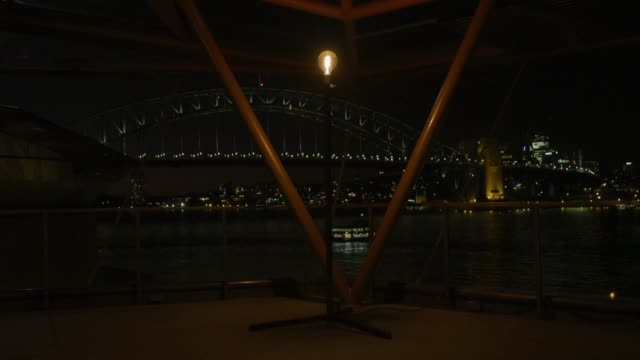 "with a view to the sydney harbour bridge, a ""ghost light"" sits atop a stand in the foyer of the joan sutherland theatre as a symbol for the people of... - オペラ座点の映像素材/bロール"