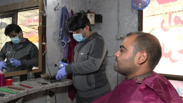with barbers remaining open for now in the gaza strip their shelfs have a box full of gloves and masks and a sanitising spray alongside their... - now open stock videos & royalty-free footage