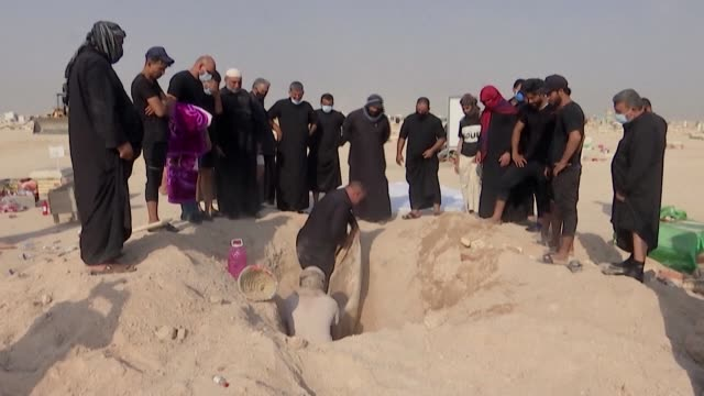 with bare hands iraqis dig into the hot desert sand to reach the corpses of their loved ones following new government orders which allow the reburial... - najaf stock videos & royalty-free footage