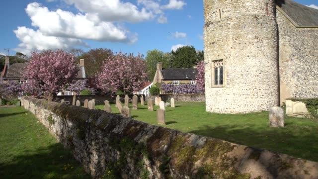 with church tower in foreground with flint walls wisteria and cherry blossom trees on a beautiful sunny day - cimitero video stock e b–roll