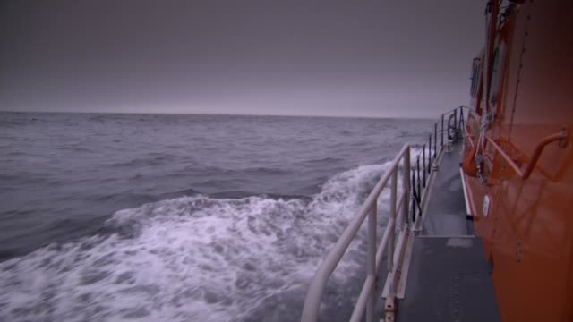 stockvideo's en b-roll-footage met ws with grey filter of seawater with rescue boat - zeegezicht