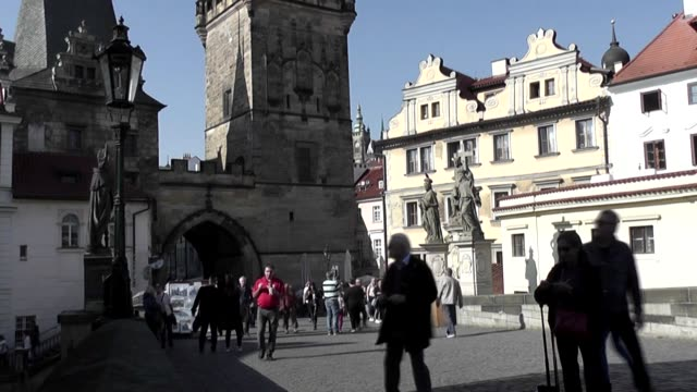 With Prague Castle seen between buildings and statues of saints in left foreground