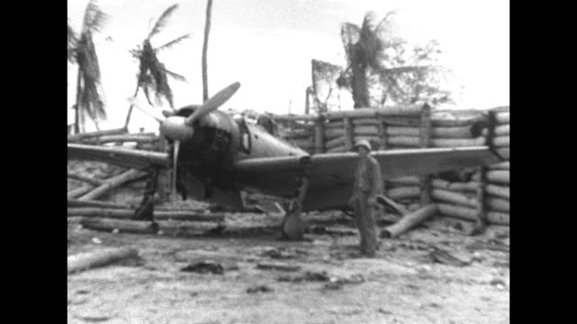 With smoke and palm trees behind US Marines crouch and move left / triangular Japanese pillbox partially buried in sand / Marine at grounded Japanese...