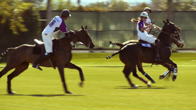 SLO MO PAN with team of polo players as they possess the ball and keep striking ball further down the field  / Indio, California, USA