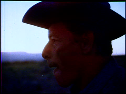 vidéos et rushes de with the sun rising in an orange sky you see quckdissolve shots of modern cowboys starting their day on the trail it's already hot in the morning as... - 1960 1969