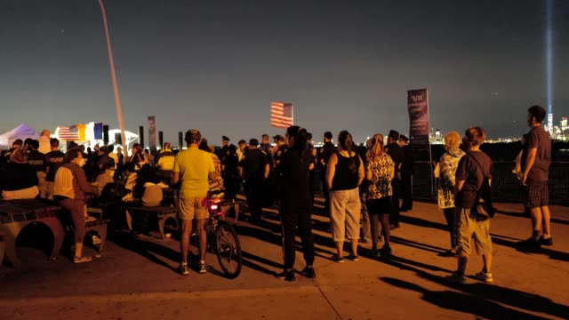 with the 'tribute in light' shining in the distance, a crowd gathers during a 9/11 community vigil at the american veterans memorial pier on... - memorial video stock e b–roll