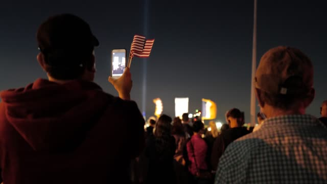 with the 'tribute in light' shining in the distance, a man records video of the 9/11 community vigil at the american veterans memorial pier on... - memorial stock videos & royalty-free footage