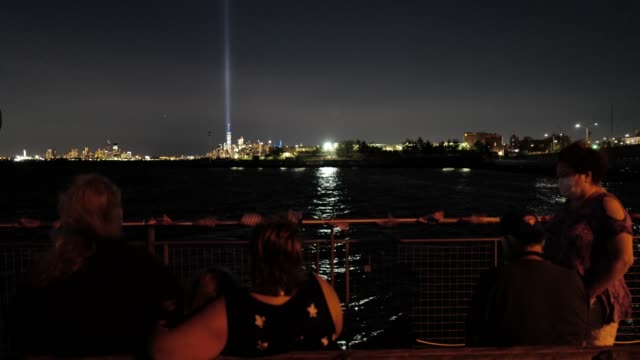 with the 'tribute in light' shining in the distance, couples and families take a moment of reflection during a 9/11 community vigil at the american... - memorial stock videos & royalty-free footage