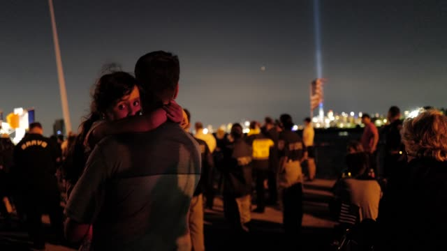 with the 'tribute in light' shining in the distance, families take a moment of reflection during a 9/11 community vigil at the american veterans... - memorial stock videos & royalty-free footage