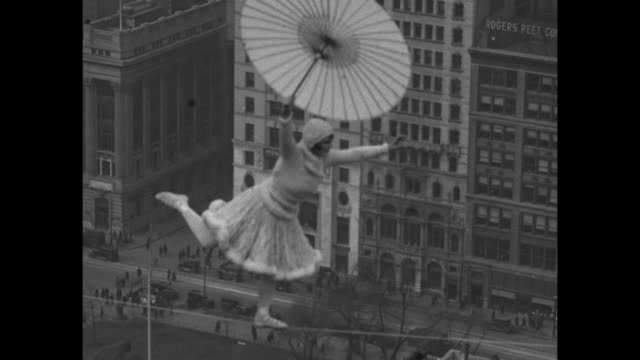 vídeos y material grabado en eventos de stock de with the woolworth building in the distance and holding a parasol bird williams performs her highwire act high over manhattan / note exact day not... - paramount building