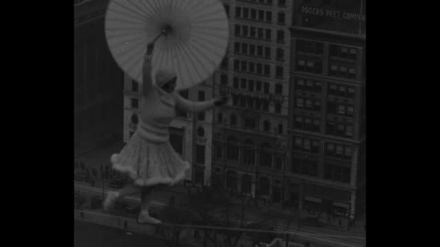 with the woolworth building in the distance and holding a parasol, bird williams performs her high-wire act high over manhattan / note: exact day not... - stunt stock-videos und b-roll-filmmaterial