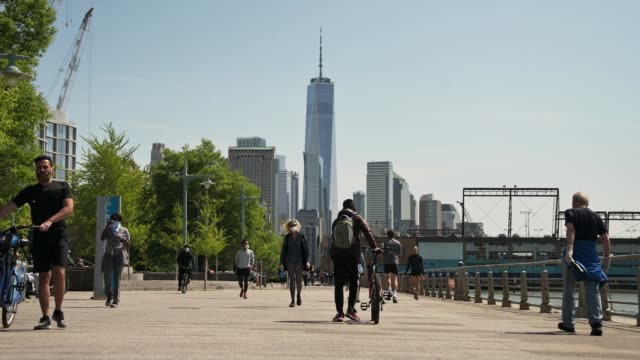 with the world trade center in the distance people wearing protective masks walk and exercise along the waterfront in hudson river park in the west... - world trade center manhattan stock videos & royalty-free footage