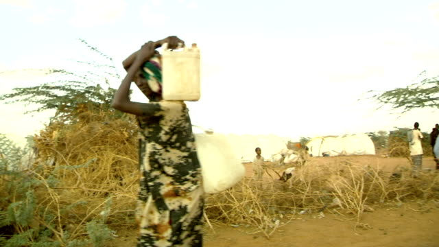 with their heads and backs at refugee camp Refugee women carrying water canisters on July 30 2011 in Dadaab Kenya