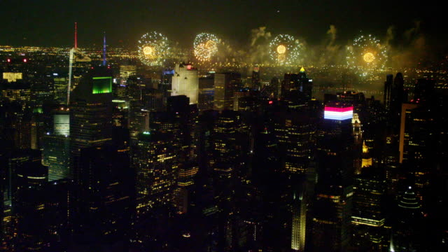 long aerial with tilt up and zoom in fireworks over hudson river with midtown manhattan in foreground at night - citigroup center manhattan stock videos & royalty-free footage