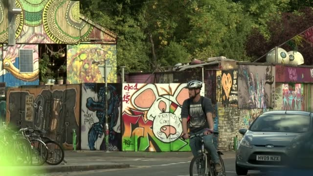 with traffic bicyclists and pedestrians pasing in front of shot in the stokes cross area of bristol england danger mouse is a british children's... - スティーブン フライ点の映像素材/bロール