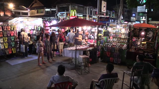vídeos de stock e filmes b-roll de with two young girl shoppers in foreground. in chang klan road in the eastern part of the city of chiang mai. the market, which operates every... - mercado noturno