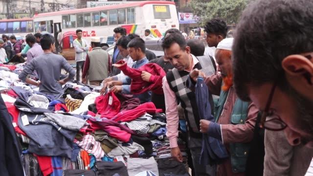 vídeos de stock e filmes b-roll de with winter getting colder, people rush to buy warm clothing at motijheel roadside shops in dhaka. - loja de roupa