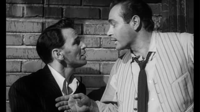1955 withdrawal symptoms force man (frank sinatra) to visit his drug dealer - bribing stock videos and b-roll footage