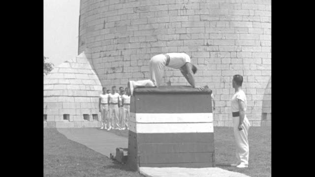 stockvideo's en b-roll-footage met vs within the walls of a stone castle complex numerous whiteclad men perform various calisthenics and jump over a striped obstacle men leapfrog over... - de brug
