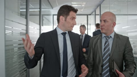 wo caucasian businessmen walking in the office hallway and having a discussion before entering an office on the left - part of a series stock videos & royalty-free footage