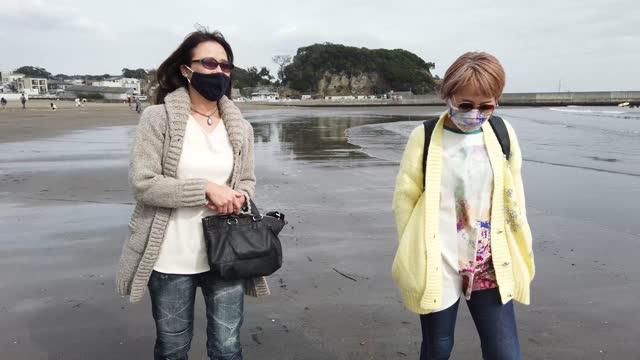 wo women wearing double masks are strolling on the beach. - 相模湾点の映像素材/bロール