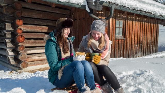 vídeos y material grabado en eventos de stock de wo young women drinking hot tea in front of a log cabin in winter - cabaña de madera