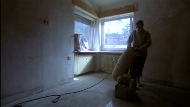 a woam operates a floor sander in an empty room. - sander stock videos & royalty-free footage