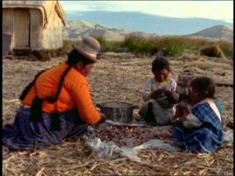 woman + 3 children sitting near hut preparing food by pot on ground / uros islands / lake titicaca - peruvian ethnicity stock videos & royalty-free footage