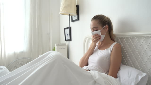 woman a cough and sick with mask on bed at home - patient stock videos & royalty-free footage