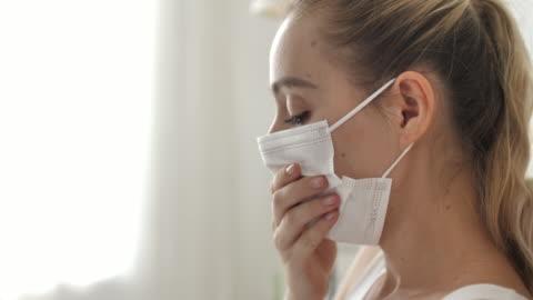 kvinna en hosta och sjuk med mask på sängen hemma - infektionssjukdom bildbanksvideor och videomaterial från bakom kulisserna