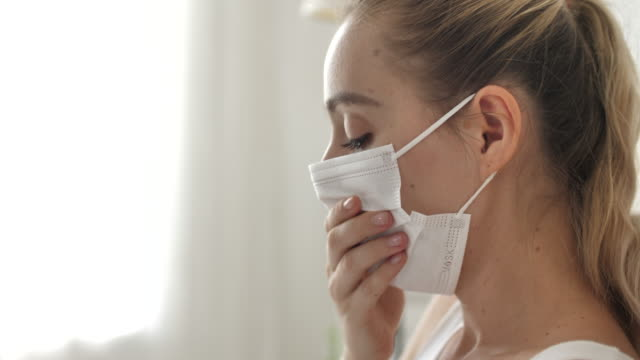 woman a cough and sick with mask on bed at home - touching stock videos & royalty-free footage